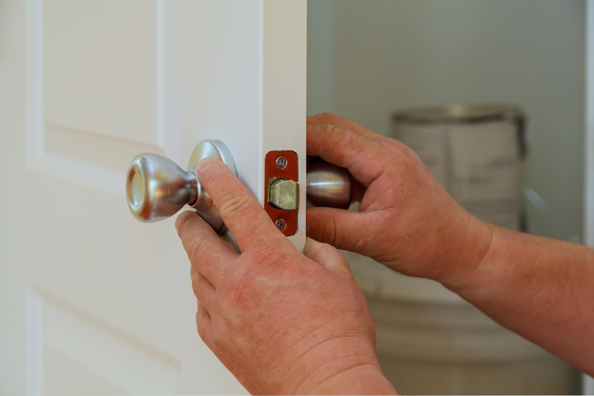 Cerrajero profesional instalando o reparando un nuevo cerrojo en la puerta de una casa