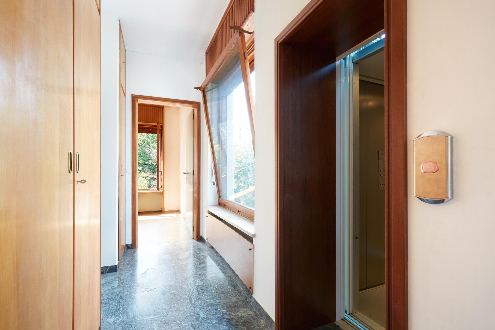 Pasillo con armario de madera, ventana y puerta de ascensor.