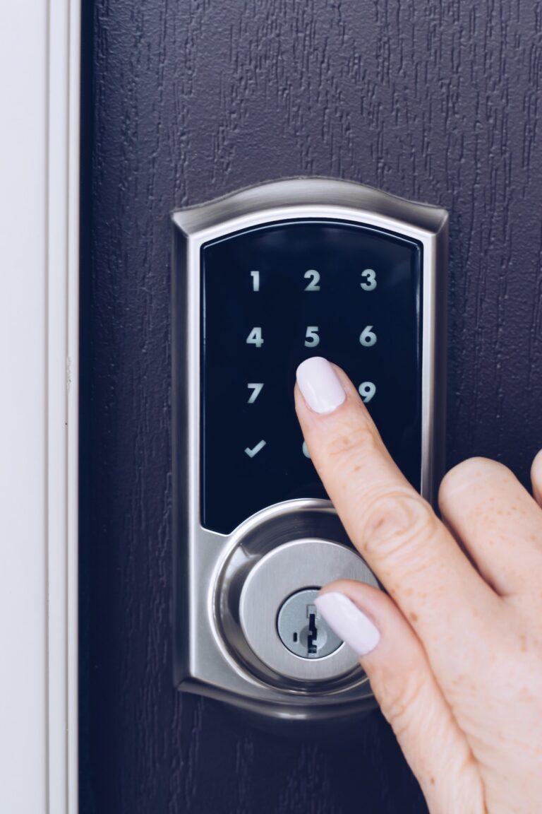 La mano de la mujer está presionando números en un teclado electrónico para abrir la puerta de una casa.